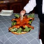 Partiendo un cochinillo tostón al clásico plato :: © Restaurante Horno de Víznar
